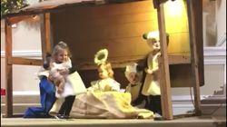 Una niña roba el niño Jesús de un Belén