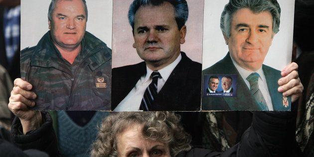 Una mujer serbia muestra la imagen del General Ratko Mladic (L), de Slobodan Milosevic (C) y de Radovan...