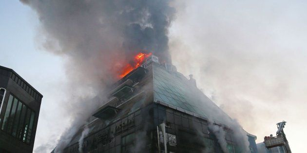 Llamas y una gran columna de humo en el edificio incendiado en