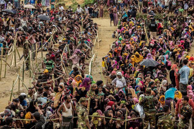 Cientos de personas refugiadas rohingyá hacen cola para recibir comida en el campo de Balukhali, al sur...