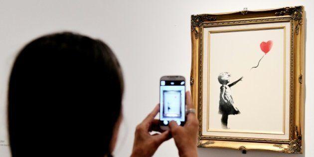Una mujer fotografía la obra 'Girl with ballon' expuesta en una galería de