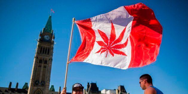 Una mujer sostiene una bandera de Canadá con la hoja de la marihuana en una imagen de