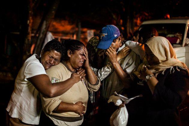 Familiares de un transexual asesinado en Tegucigalpa lloran frente a la morgue de la ciudad en el momento...