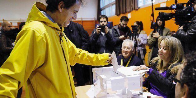 Un hombre vota vestido de amarillo (color elegido en solidaridad con Jordi Sánchez y Jordi Cuixart) en...