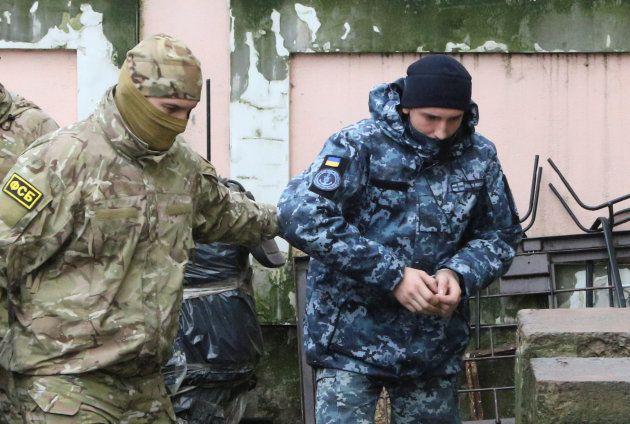 Un miembro de las fuerzas de seguridad rusas acompaña al marine ucraniano