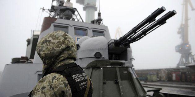 Un soldado ucraniano junto a un buque en el mar de