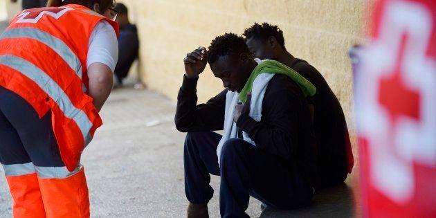 Un miembro de la Cruz Roja asiste a varios migrantes en la puerta de un gimnasio usado como centro de...