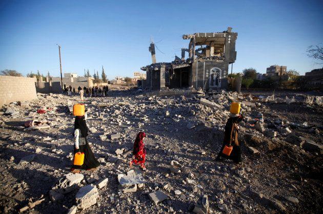 Un grupo de yemeníes camina portando agua entre las ruinas de su barrio en la capital, bombardeado por...