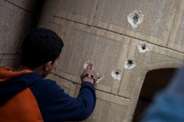 Un curioso mete el dedo en el agujero de uno de los impactos de bala en unmuro próximo a la iglesia Mar...