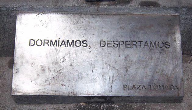 Placa original del Movimiento 15-M situada a los pies del caballo de Carlos III en la Puerta del Sol...