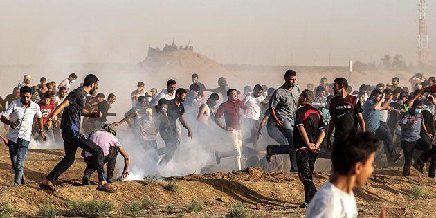 Decenas de palestinos se ponen a cubierto del gas lacrimóeno lanzado por soldados israelíes durante protestas...