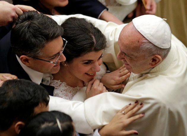 El papa Francisco abraza a una pareja de recién casados, durante una audiencia general en el Vaticano,...