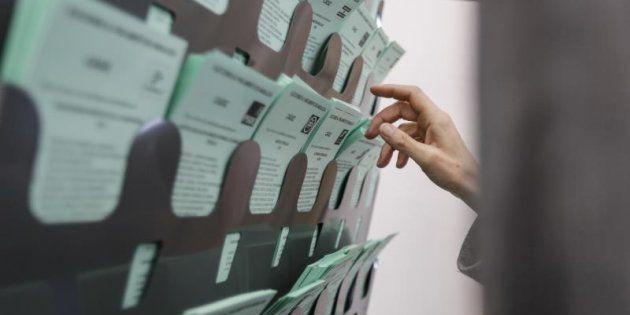 Una votante escoge la papeleta para elegir a su candidato hoy en el colegio electoral ubicado en la biblioteca...