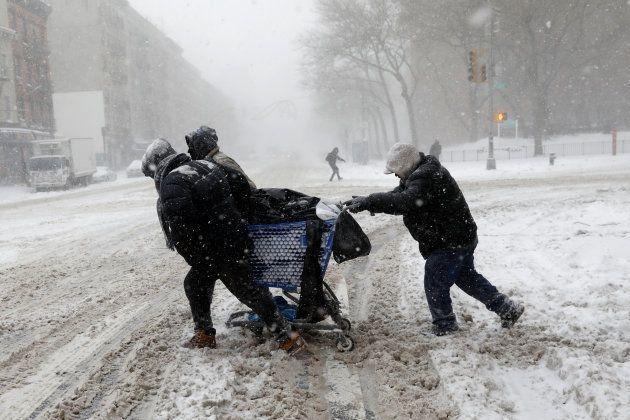 Un grupo de personas lucha contra el viento en Nueva York para empujar un carrito de la