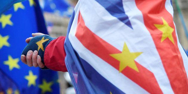 Un hombre con las banderas de Reino Unido y la UE