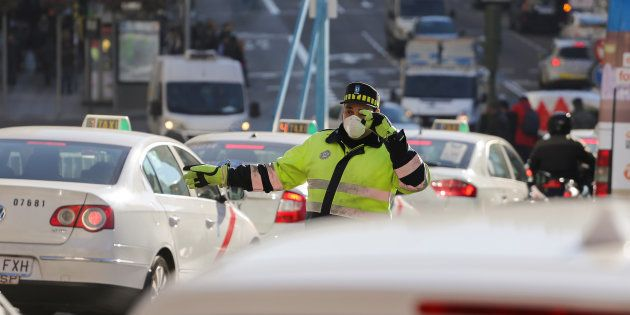 A traffic policeman wears a mask while directing traffic during traffic restrictions intended to curb...