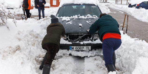 Dos personas rescatan un coche de la nieve en Torrecaballeros, en la provincia de Segovia. CESAR MANSO/AFP/Getty