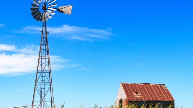 A photograph of a winmill and hut against a blue sky, taken in Kansas.
