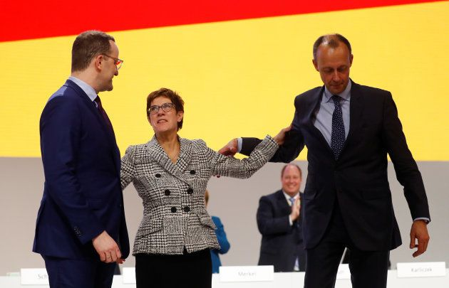 Annegret Kramp-Karrenbauer reacts with fellow candidates Jens Spahn and Friedrich Merz after being elected...