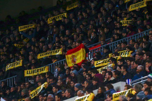 Un aficionado muestra una bandera de España entre los mensajes a favor de la libertad de los presos por...