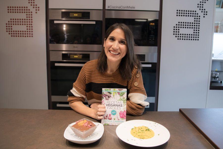Gloria Carrión posa con dos de sus platos y su libro 'Recetas veganas fáciles' en la librería gastronómica...