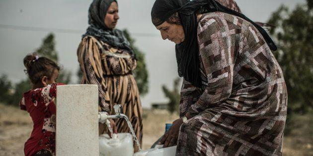 Unas mujeres llenan unas garrafas con agua en