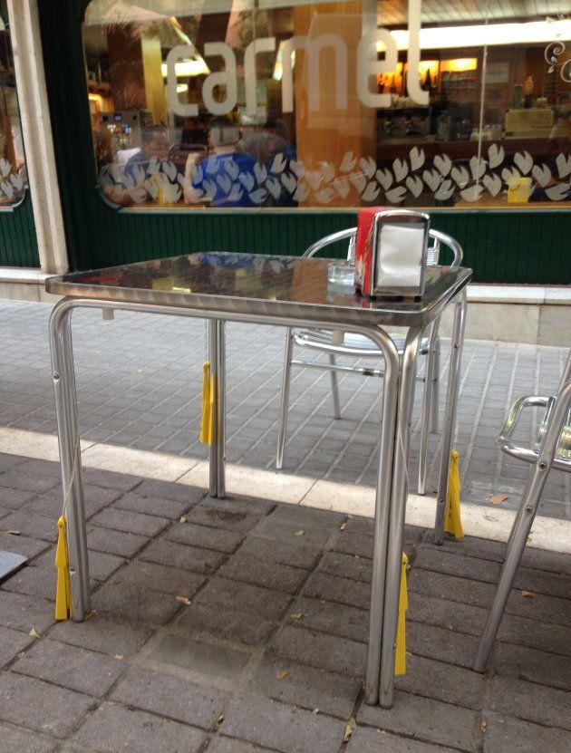 Abanicos atados a las patas de una mesa en la terraza de un bar. Barrio de Sarrià, Barcelona (Agosto
