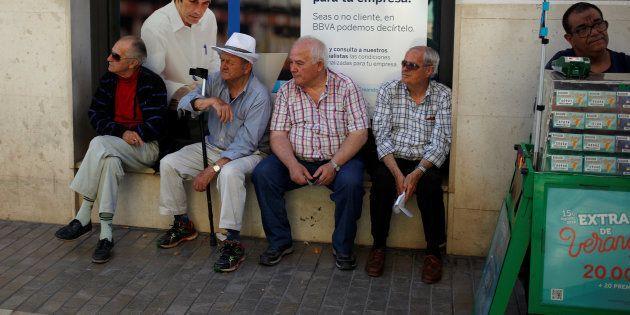 Un grupo de pensionistas sentados delante de una oficina del BBVA en