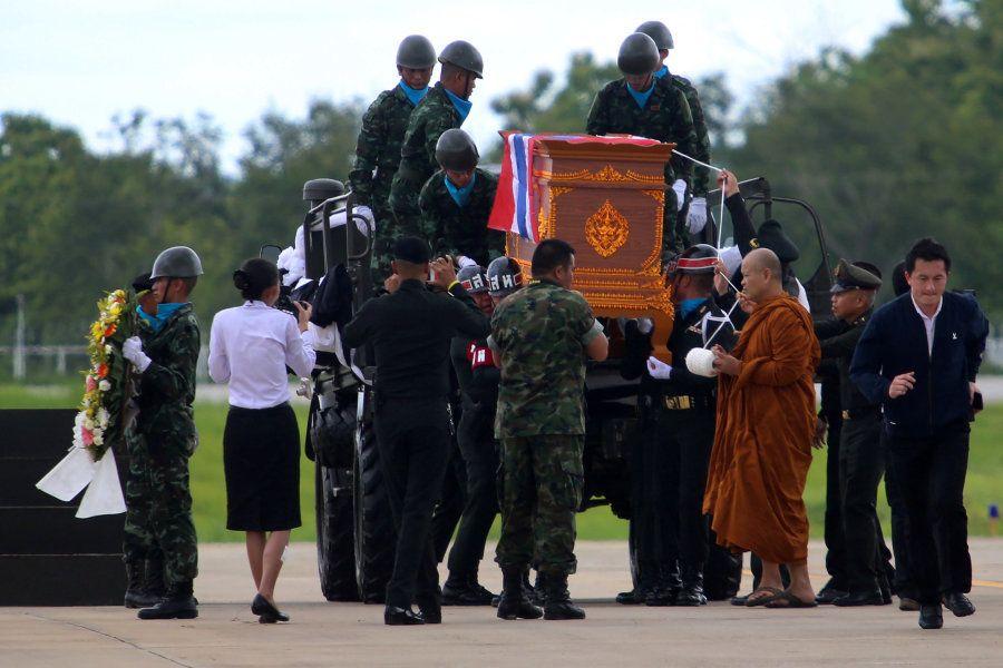Los equipos de rescate y un monje budista portan el féretro del