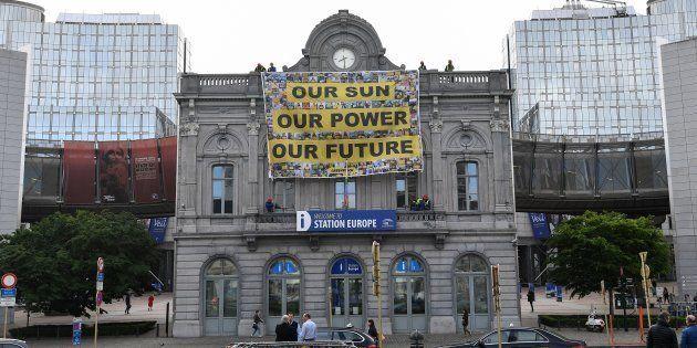 Un grupo de activistas de Greenpeace cuelga un cartel frente al Parlamento Europeo durante la ronda de...