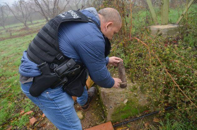 Uno de los agentes, tras localizar un proyectil de artillería en un campo de árboles