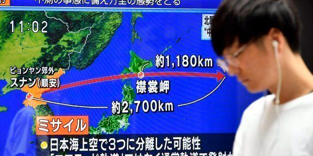 Un peatón en Tokio pasa junto a una pantalla que describe el lanzamiento del misil