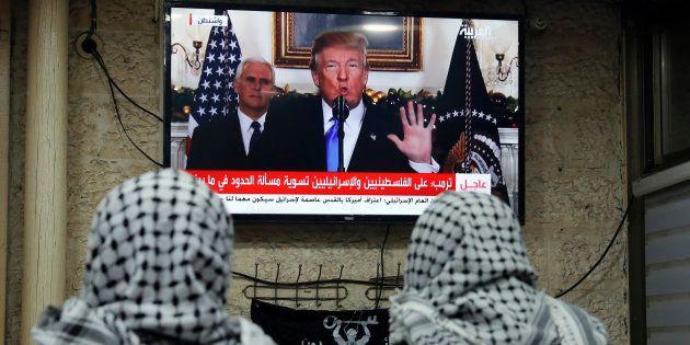 Dos hombres palestinos siguen la intervención de Trump en la que anuncia el reconocimiento de Jerusalén...