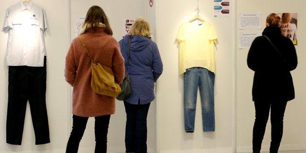 Un grupo de visitantes repasa las prendas de la