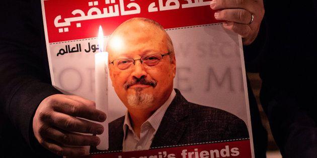 Un manifestante porta una vela y una pancarta en solidaridad con Jamal Khashoggi ante el consulado saudí...