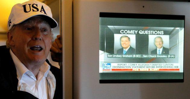 Trump habla con periodistas a bordo del Air Force One junto a una pantalla de televisión que emite un...