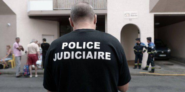 Un agente de la Policía Judicial, junto al edificio donde han muerto cinco miembros de la misma familia...