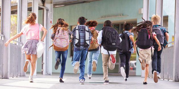 Un grupo de niños corre para salir del colegio, en una imagen de