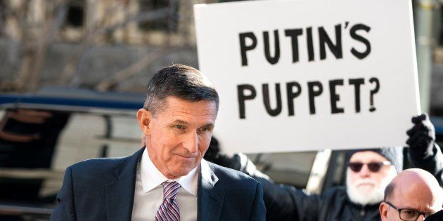 Flynn a su llegada al Tribunal Federal ante un manifestante (c) con una pancarta que reza: ''¿La marioneta...