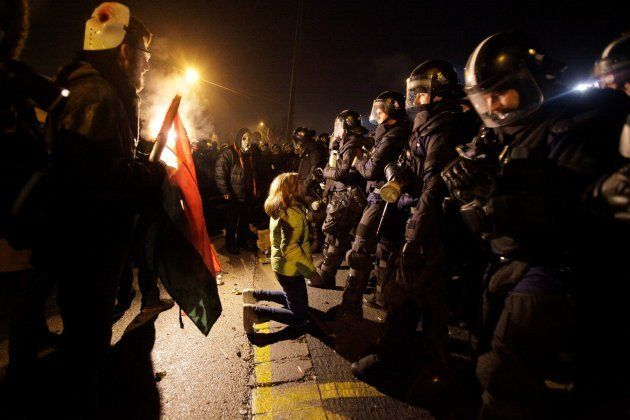 A participant knees in front of the riot police line outside the headquarter of the Hungarian state television...