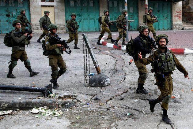 Soldados israelíes patrullan por las protestas en Hebron por la visita de Mike