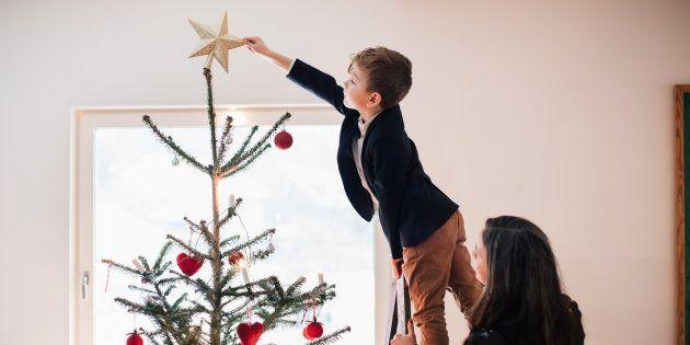 Un niño coloca la estrella en el árbol de