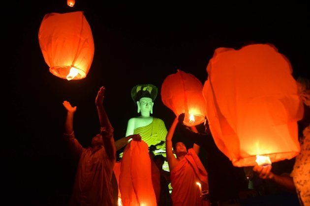 AGARTALA, TRIPURA, INDIA - 2018/11/14: Buddhist monk and devotes are seen flying sky lamps in front of...