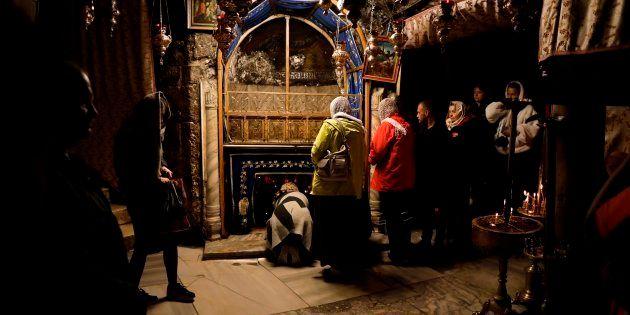 Un grupo de peregrinos se inclina en el lugar en el que la tradición marca el nacimiento de Jesús, en...