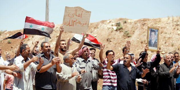 Un grupo de civiles celebra la entrada de las tropas del régimen en