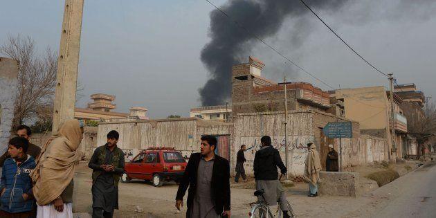 Civiles afganos en las inmediaciones del lugar del ataque, donde se eleva una columna de