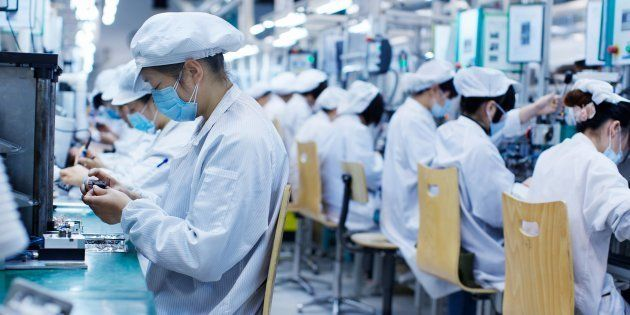 Group of workers at small parts manufacturing factory in China, wearing protective clothing, hats and