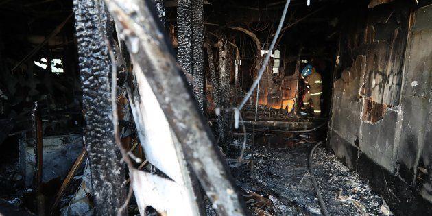 Los bomberos apagan los restos del fuego en un cuarto de hospital