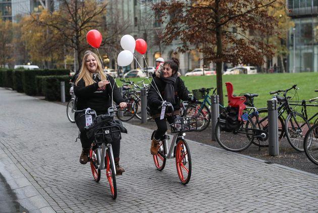 Dos trabajadoras de la empresa china Mobike estrenando el servicio de alquiler de bicicletas implantado...