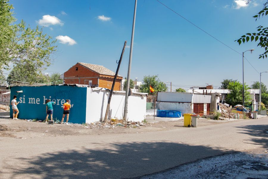 Tres voluntarias pintan uno de los últimos muros en el sector
